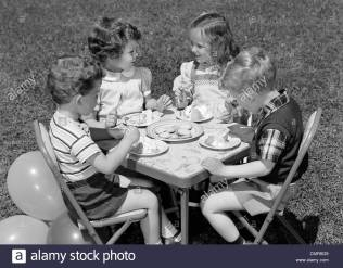 1950s-pair-of-boys-girls-at-table-on-lawn-eating-cookies-ice-cream-cmr8g9