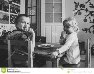grayscale-photo-two-kids-sitting-dining-table-chairs-115203161